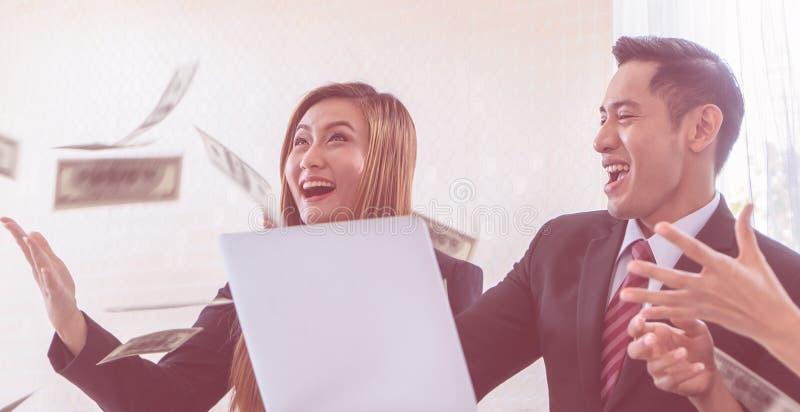 企业队伙伴通过投金钱庆祝 免版税库存照片
