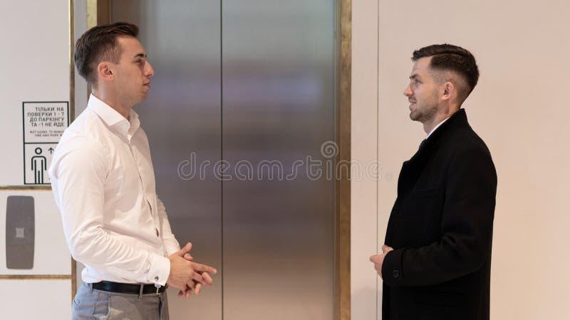 企业队在电梯附近的小组身分 在一个电梯附近的商人在办公室 免版税库存照片