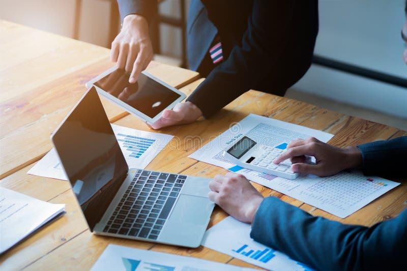 企业队礼物 年轻商人有会议和工作在现代办公室 膝上型计算机、片剂和文件在工作 库存照片
