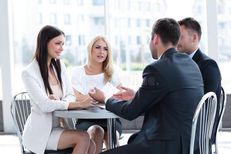 企业队讨论企业问题,坐在桌上在咖啡馆 库存图片
