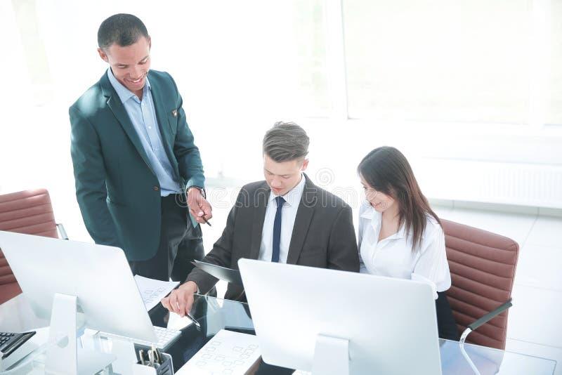 企业队谈论商业文件在工作场所 免版税库存照片