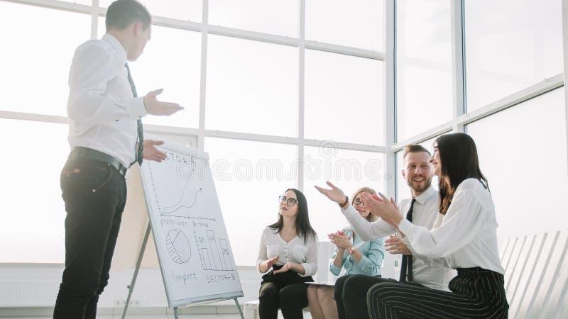 企业队赞许报告人在一份简报在新的办公室 库存图片