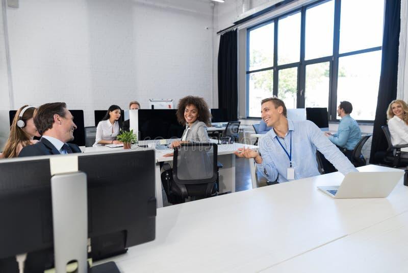 企业队运作的概念现代露天场所办公室,买卖人坐在计算机的小组工友谈话  免版税库存图片