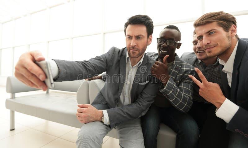 企业队采取在商业中心的大厅的selfies 库存图片
