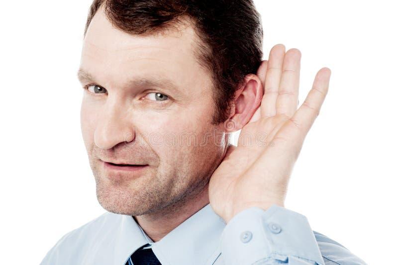 企业经营者在耳朵附近的举行手 库存照片