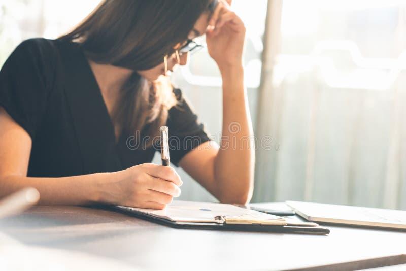 企业womanlooking的智能手机和举行文件在手上 露天场所顶楼办公室,年轻女商人 免版税库存照片