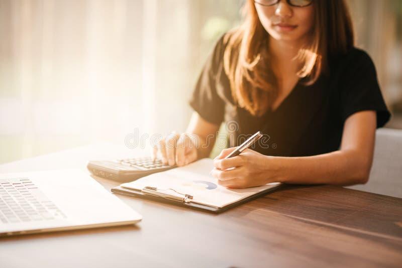 企业womanlooking的智能手机和举行文件在手上 露天场所顶楼办公室,年轻女商人 图库摄影