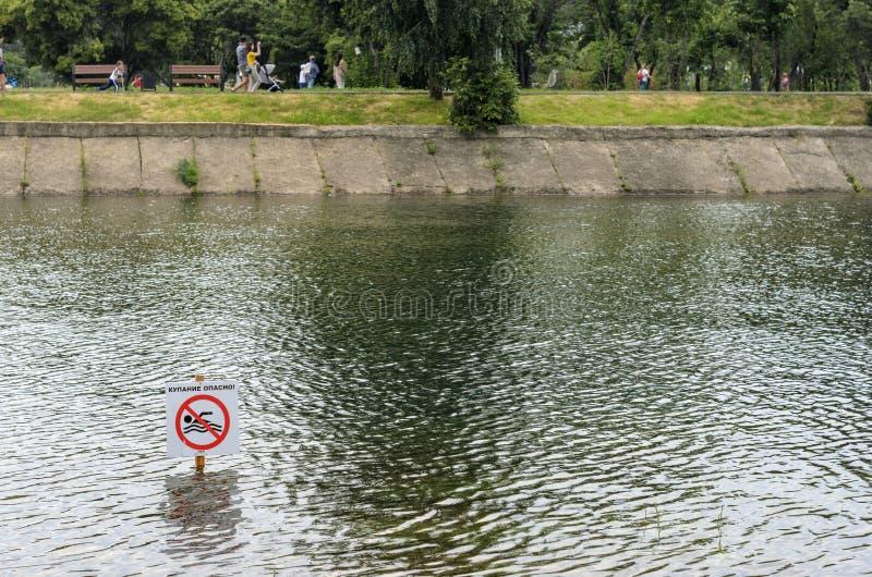 伊尔库次克,俄罗斯- 2019年7月15日:人们走靠近河在公园,游泳是危险标志 免版税库存图片