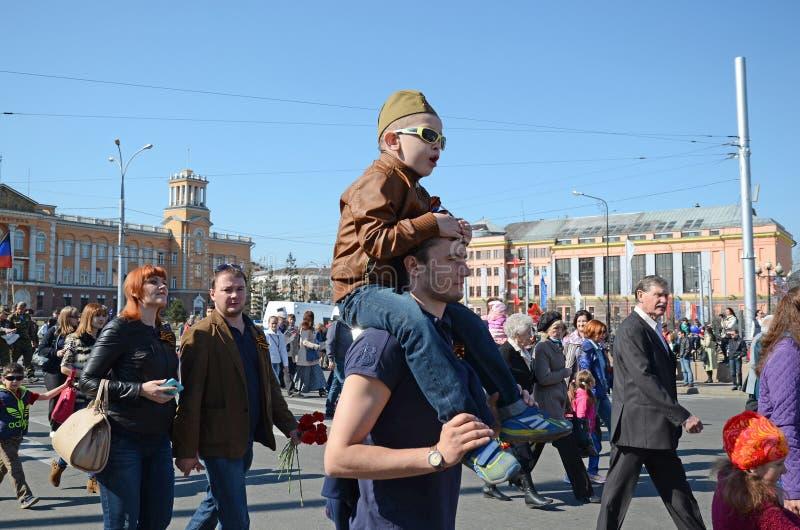 伊尔库次克,俄罗斯- 2015年5月9日:父亲的年轻男孩在胜利天队伍担负在伊尔库次克 免版税库存图片