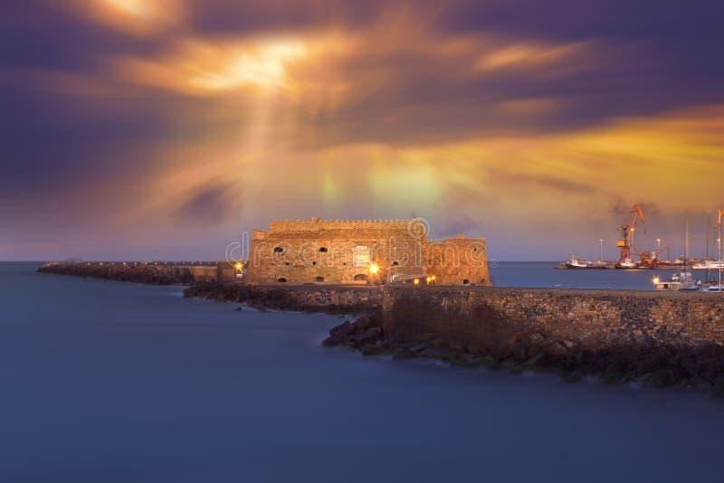 伊拉克利翁老港口有威尼斯式Koules堡垒、小船和小游艇船坞的在晚上,克利特 图库摄影
