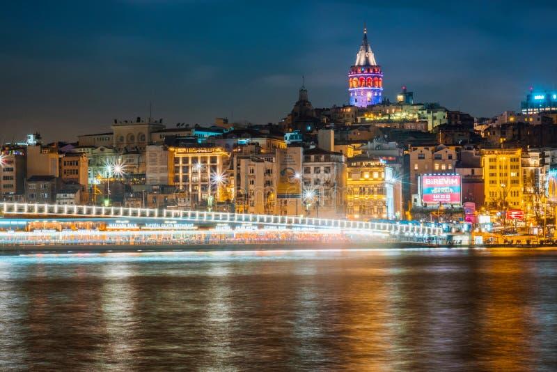 伊斯坦布尔都市风景加拉塔石塔夜视图与漂浮游船的在博斯普鲁斯海峡,伊斯坦布尔土耳其 库存照片