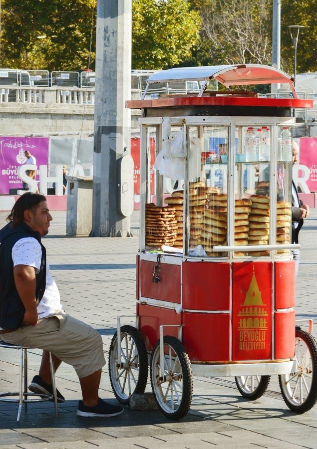 伊斯坦布尔,土耳其,2018年9月18日 传统土耳其百吉卷-选址在一辆卡车旁边的simits的卖主在塔克西姆广场 免版税库存照片