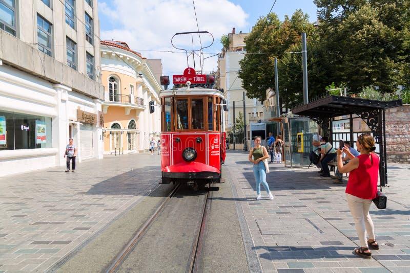 伊斯坦布尔,土耳其- 2018年8月:做照片的少女游人减速火箭的电车在Istiklal街道 红色电车Taksim-Tunel 图标 库存图片