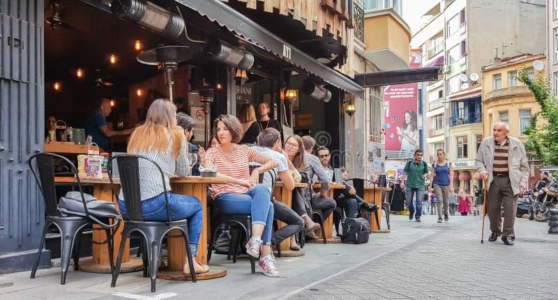 伊斯坦布尔,土耳其- 2017年6月02日:坐在酒吧的人们在伊斯坦布尔市,土耳其著名Kadikoy区  免版税库存照片