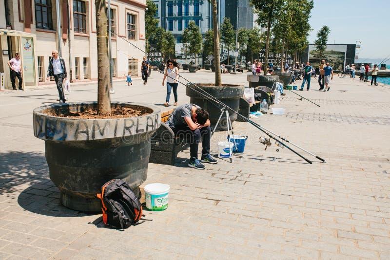 伊斯坦布尔, 2017年6月17日:传统土耳其渔爱好 渔夫是疲乏或沮丧的一个当地居民 免版税库存照片