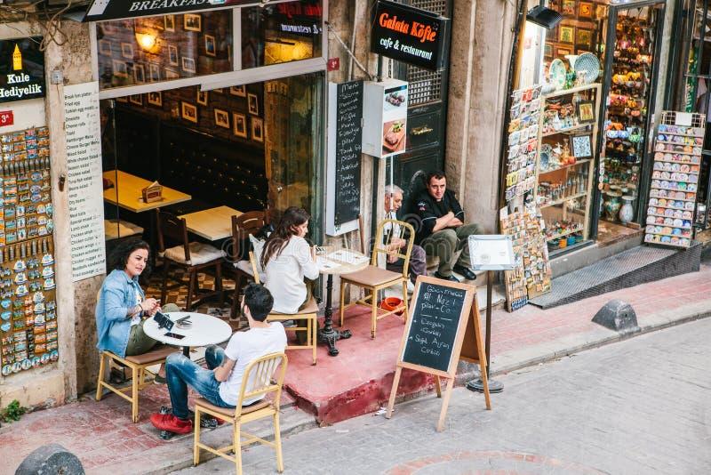 伊斯坦布尔, 2017年6月15日:坐加拉塔Kofte餐馆外的人们 在游人和当地人民中的一个普遍的地方 免版税库存图片