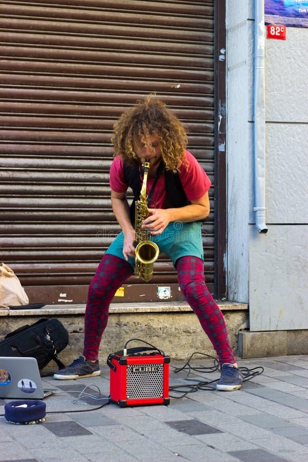 伊斯坦布尔,Istiklal街/土耳其9 5 2019年:在Istiklal街的街道音乐家执行的萨克斯管 免版税库存照片