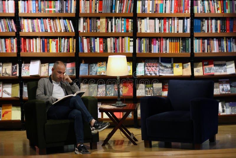 伊斯坦布尔,Istiklal街/土耳其9 5 2019年:盐贝伊奥卢艺术中心,读在书架前面的人一本书 免版税库存图片