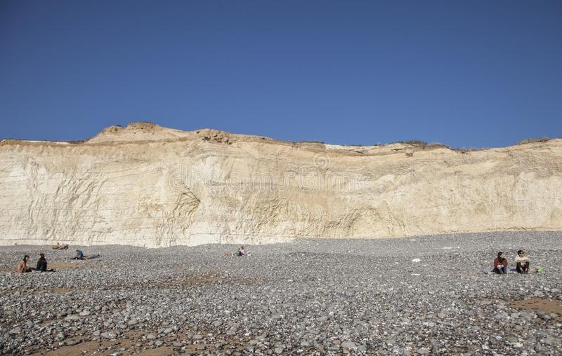 伊斯特本,英国,东萨塞克斯郡,英国-七个姐妹峭壁和游人在一好日子 库存照片