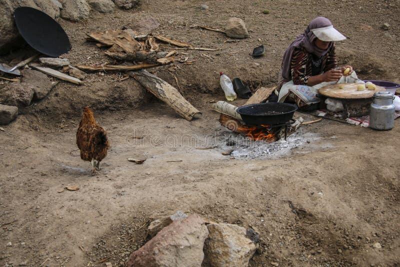 伊朗妇女在山的一开火做面包蛋糕 免版税库存图片