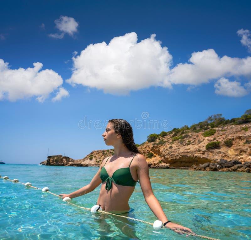 伊维萨岛在清楚的水海滩放松的比基尼泳装女孩 免版税库存图片