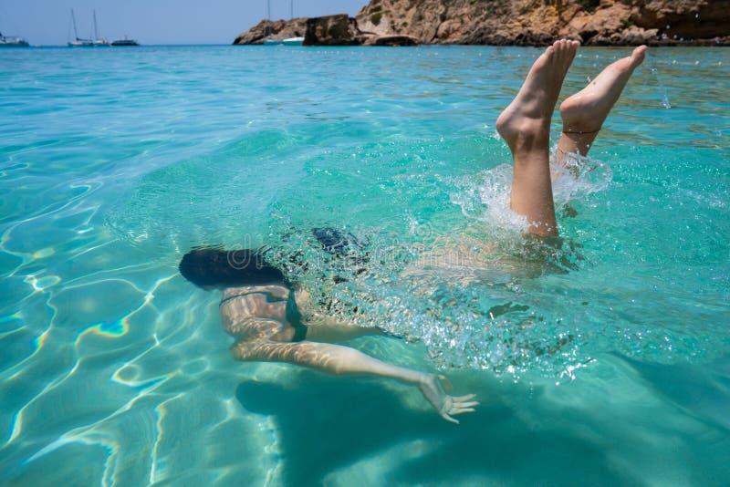 伊维萨岛游泳清楚的水海滩的比基尼泳装女孩 免版税库存照片