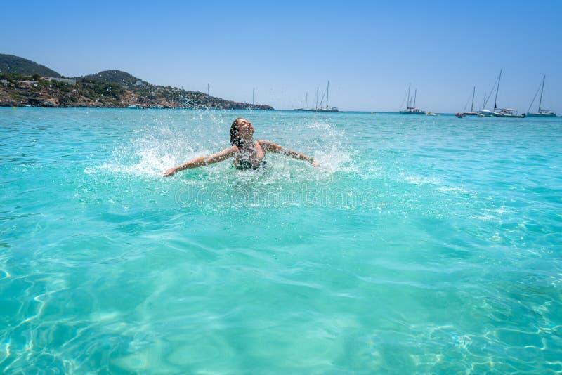 伊维萨岛飞溅清楚的水海滩的比基尼泳装女孩 免版税库存图片
