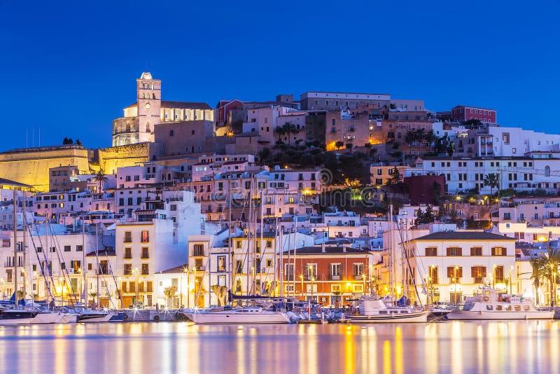 伊维萨岛Dalt维拉街市在与光反射的晚上在水,伊维萨岛,西班牙中 免版税库存照片
