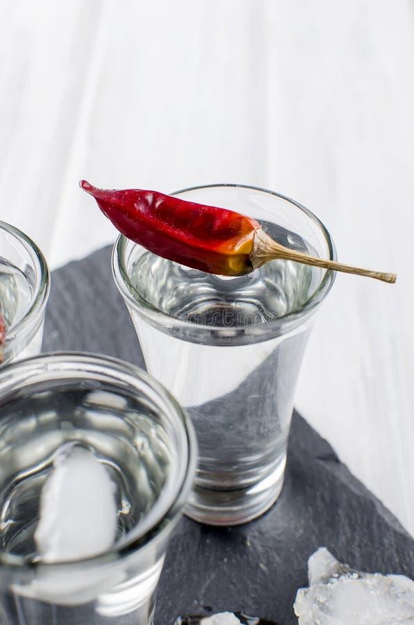 伏特加酒在白色桌上的射击withchili 库存照片