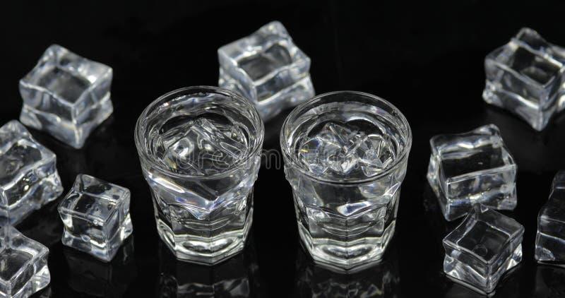 伏特加酒射击与冰块的反对黑背景 库存图片