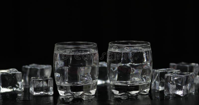 伏特加酒射击与冰块的反对黑背景 免版税库存图片