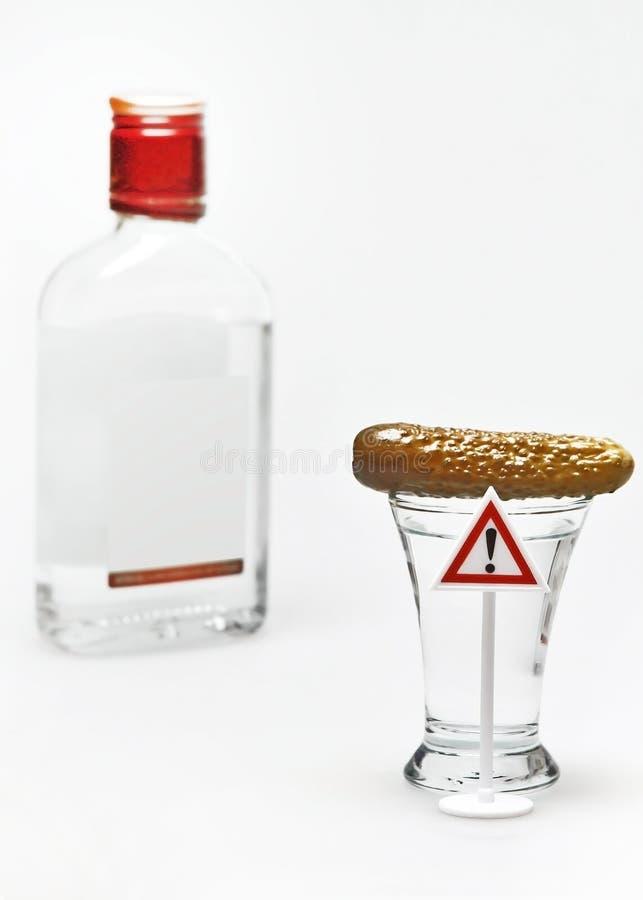 伏特加酒射击用黄瓜和警告惊叫标志 免版税库存照片