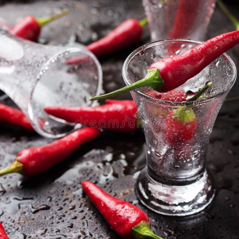 伏特加酒射击了用在生锈的难看的东西桌上的辣椒 免版税图库摄影