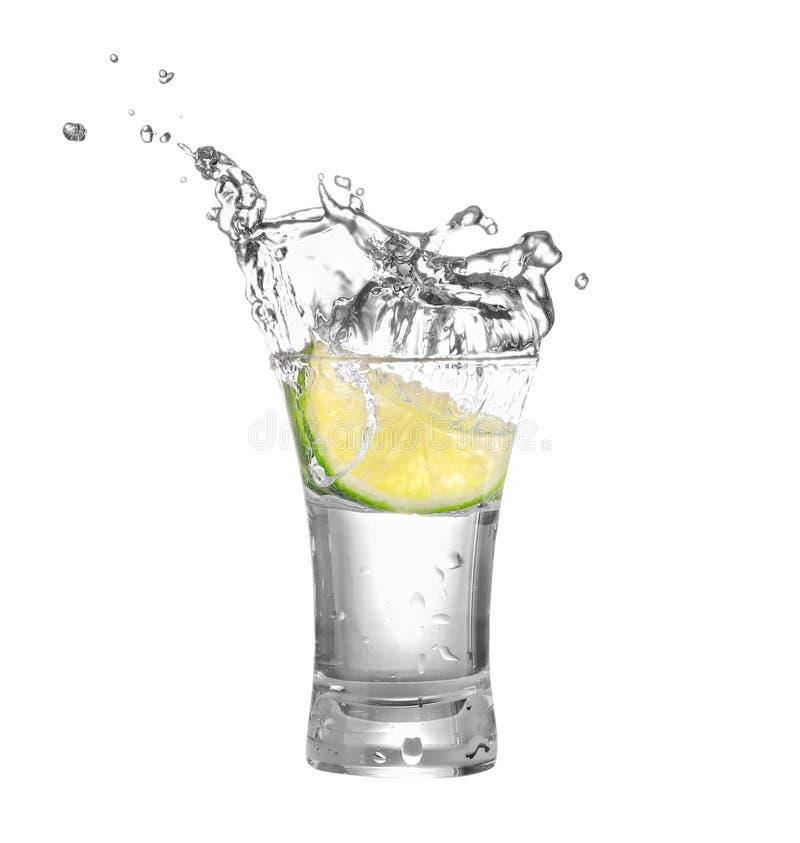 伏特加酒或龙舌兰酒在玻璃与石灰切片 免版税库存照片