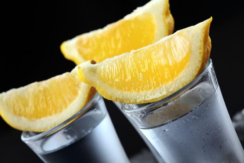 伏特加酒 射击,玻璃用伏特加酒用柠檬 黑暗的石背景 特写镜头 选择聚焦 库存图片