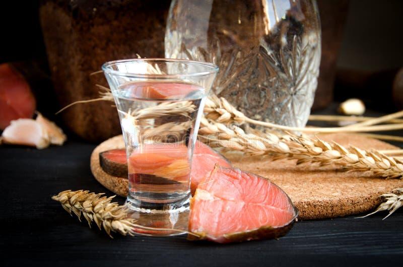 伏特加酒玻璃蒸馏瓶麦子三文鱼大蒜特写镜头 库存照片