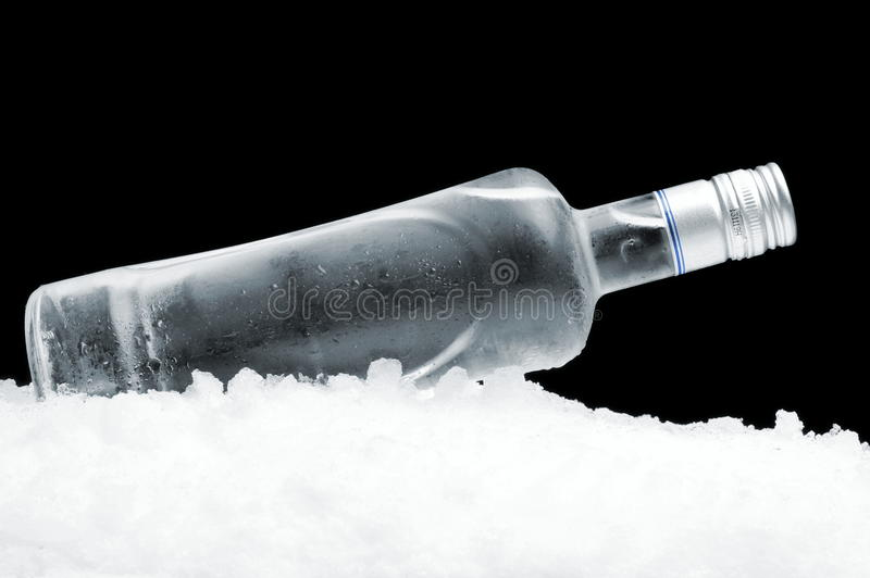 伏特加酒说谎在黑背景的冰的瓶 免版税库存图片