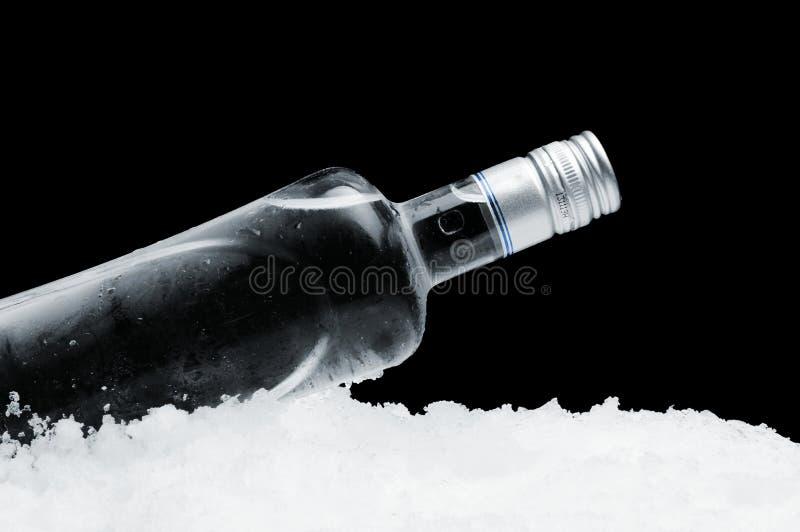 伏特加酒说谎在黑背景的冰的瓶 免版税图库摄影