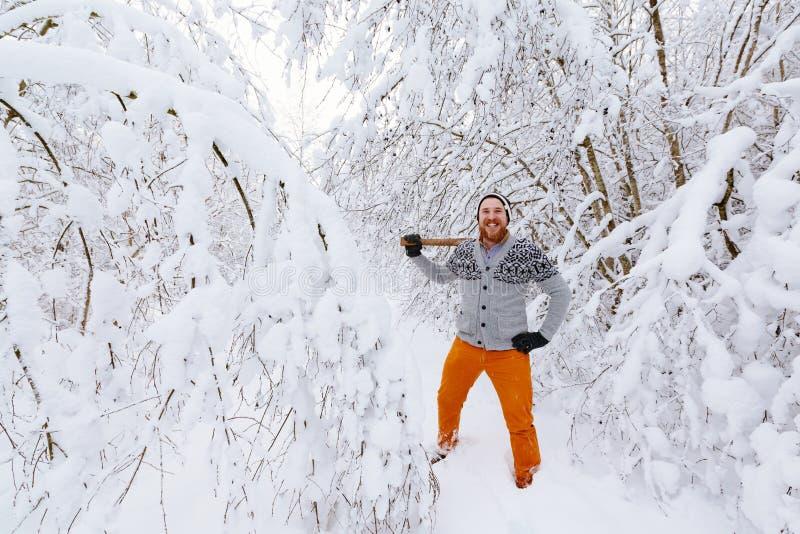 伐木工人在多雪的冬天森林里 免版税库存照片