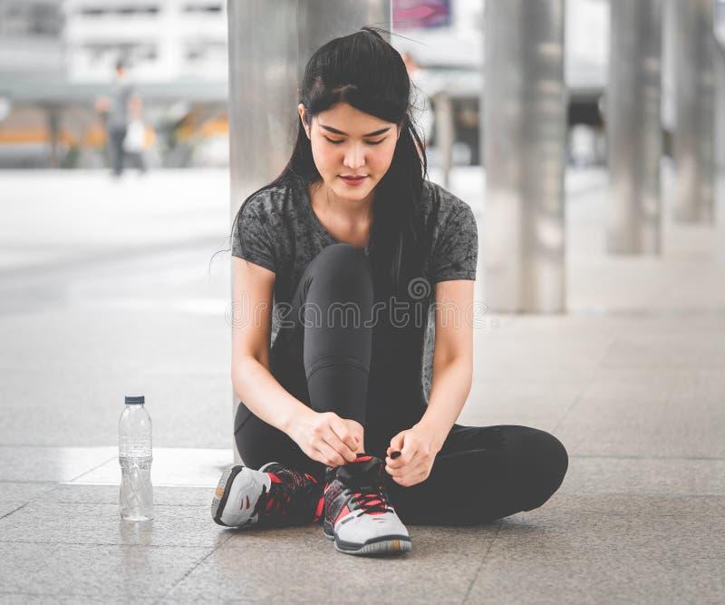 休假和tighting鞋带的亚洲妇女赛跑者 免版税库存图片