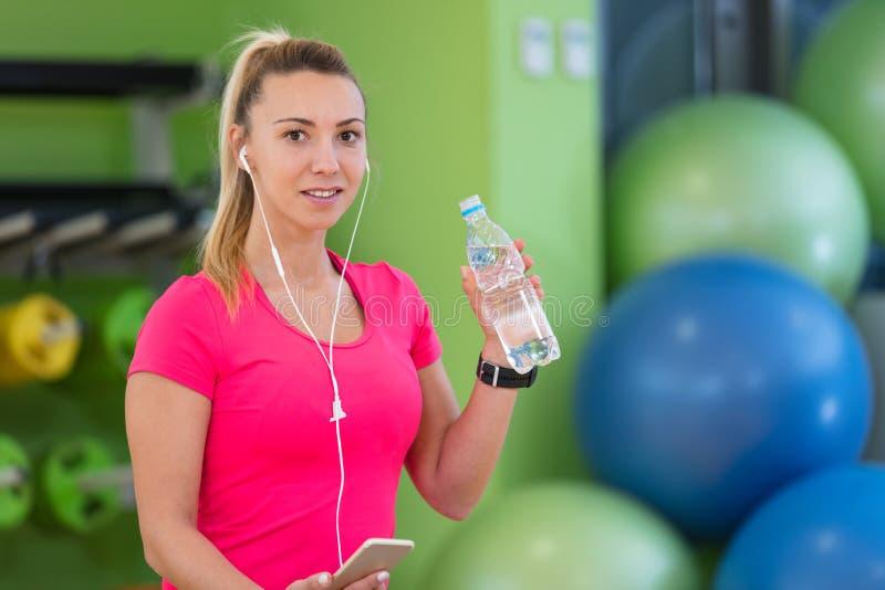 休假的一个少妇在健身房坐与一个瓶的一个pilates球水 免版税库存照片