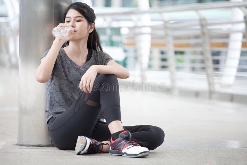 休假的亚裔健身妇女在行使喝与在街道上的一个水瓶的锻炼以后在都市城市 疲乏的体育 库存图片