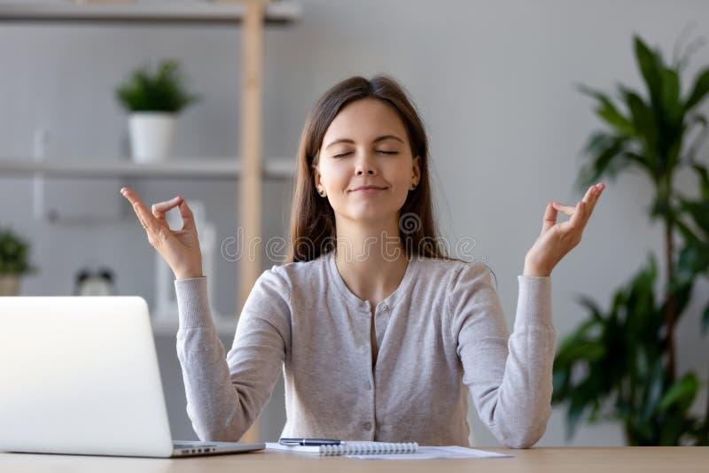 休假的安静年轻女人做瑜伽锻炼在工作场所 免版税库存图片