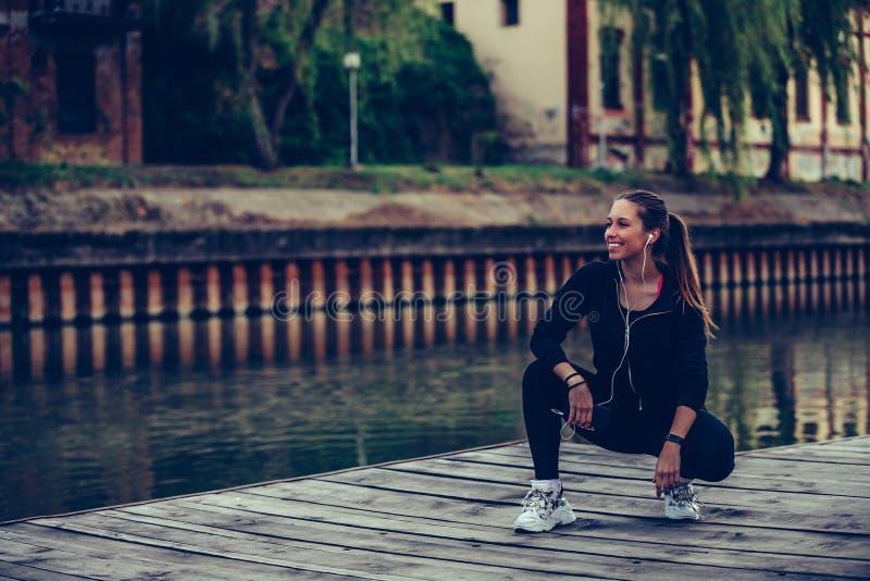 休假的年轻女人在跑步由河以后 库存照片