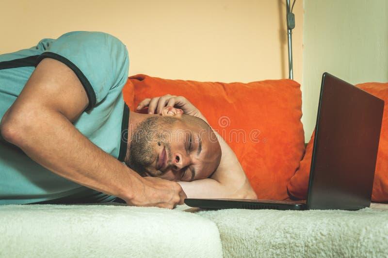 休假的年轻疲乏的人和睡着了在与他的膝部上面计算机的床上在艰苦以后和长期网上工作,黑暗的图象 免版税库存图片