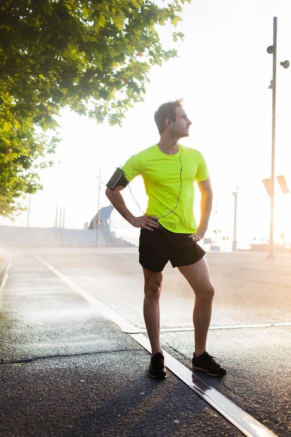 休假的英俊的运动人在跑以后外面在公园,当看时 免版税库存图片