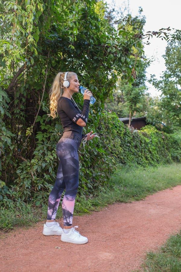 休假的运动的妇女,当饮用水时 库存照片