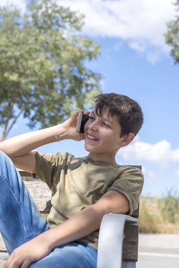 休假的长凳的男小学生使用机动性 免版税库存照片