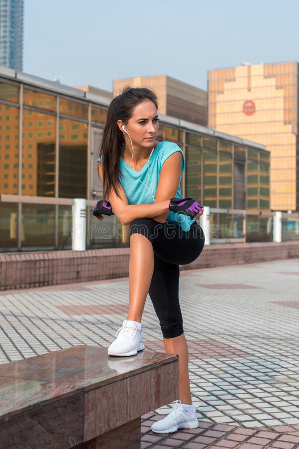 休假的年轻人适合的妇女在行使或跑以后 站立和基于户外城市街道的健身女孩 库存照片