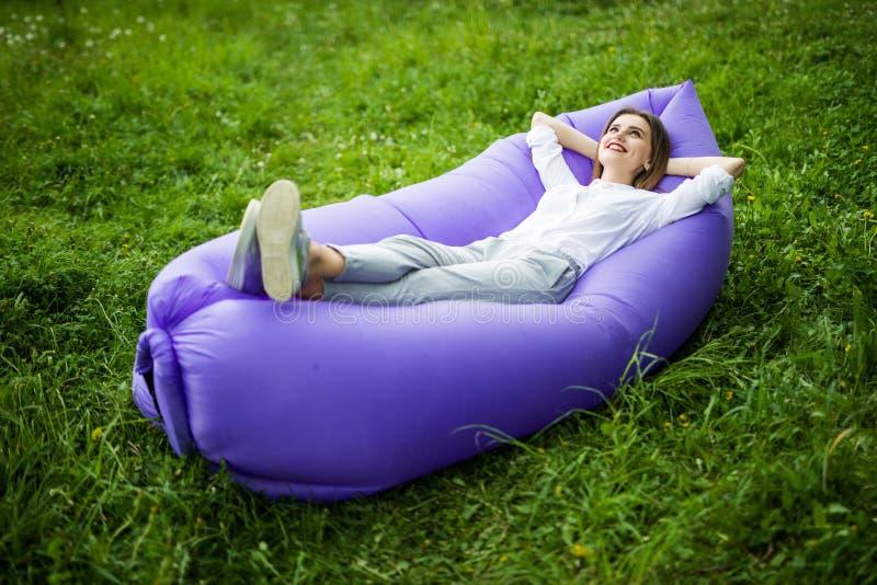 休假 相当说谎在可膨胀的沙发lamzac的少妇,当基于草在太阳的时公园 库存图片